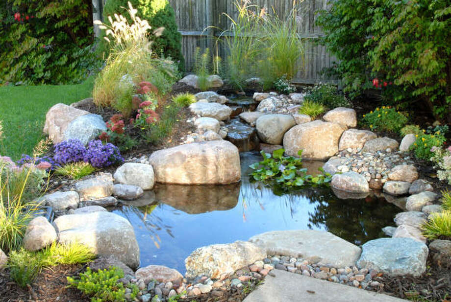 THE LIFE AQUATIC: Water features can be used anywhere, but many place the ecosystem ponds in the back yard close to a sitting area.