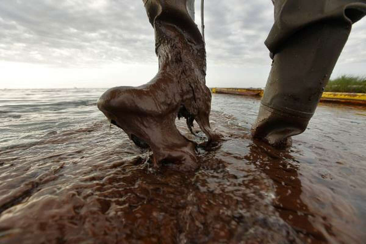 Plaquemines (La.) Parish coastal zone director P.J. Hahn lifts his boot out of thick beached oil at Queen Bess Island in Barataria Bay.