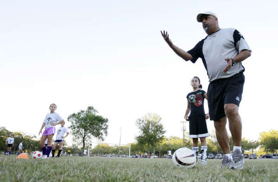 Carlos Lessa da instrucciones a las jóvenes futbolistas que dirige durante una práctica en Bear Creek Park, en Katy. Photo: Karen Warren, La Voz