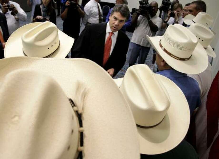 "Texas Gov. Rick Perry greets sheriffs at a law enforcement conference in Fort Worth on Monday. The Republican said he supports ""the men and women who wear the badge.""  Photo: Paul Moseley, AP"