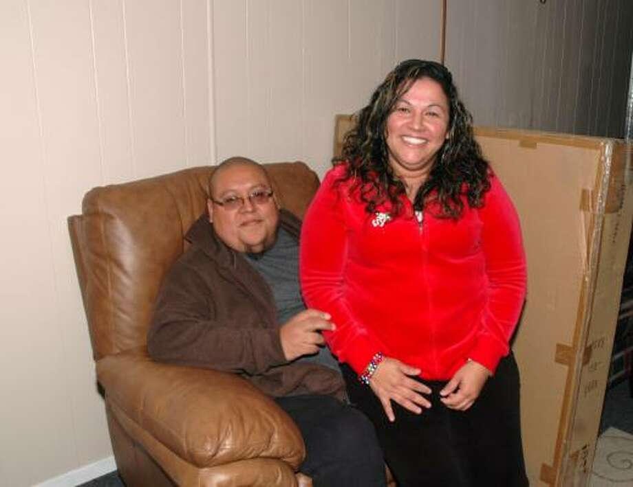 GRATEFUL COUPLE: Omar Gutierrez and his wife, Connie, sit on a new recliner donated to them by Gallery Furniture. Photo: George Wong, For The Chronicle