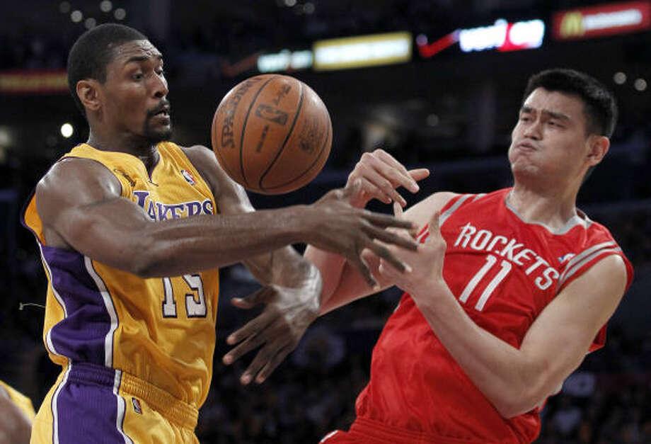 El chino Yao Ming, der., disputa un balón con su ex compañero de los Rockets Ron Artest, quien en la apertura de la temporada salió airoso en la victoria de los Lakers. Photo: Chris Carlson, AP