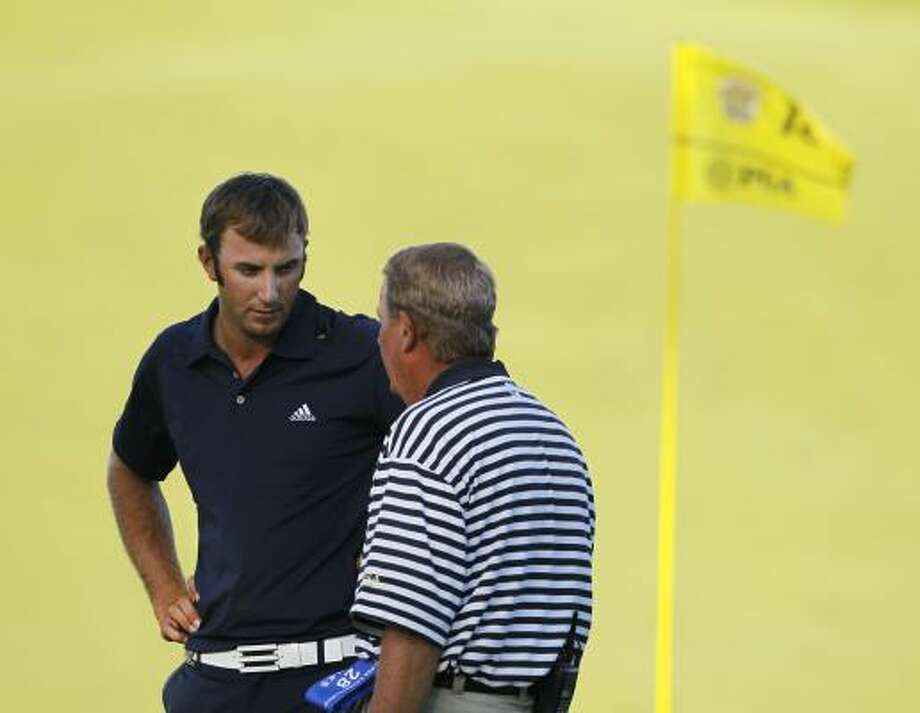 Rules official David Price informs Dustin Johnson of the penalty for grounding his club in a bunker. Photo: Charlie Neibergall, AP