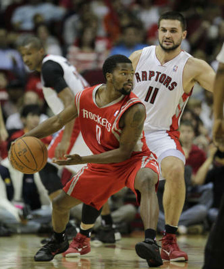 Dec. 31: Rockets 114, Raptors 105 Rockets guard Aaron Brooks (0) tries to pass against the defense of Toronto's Linas Kleiza during the first half of Friday's game at Toyota Center. Photo: Karen Warren, Chronicle