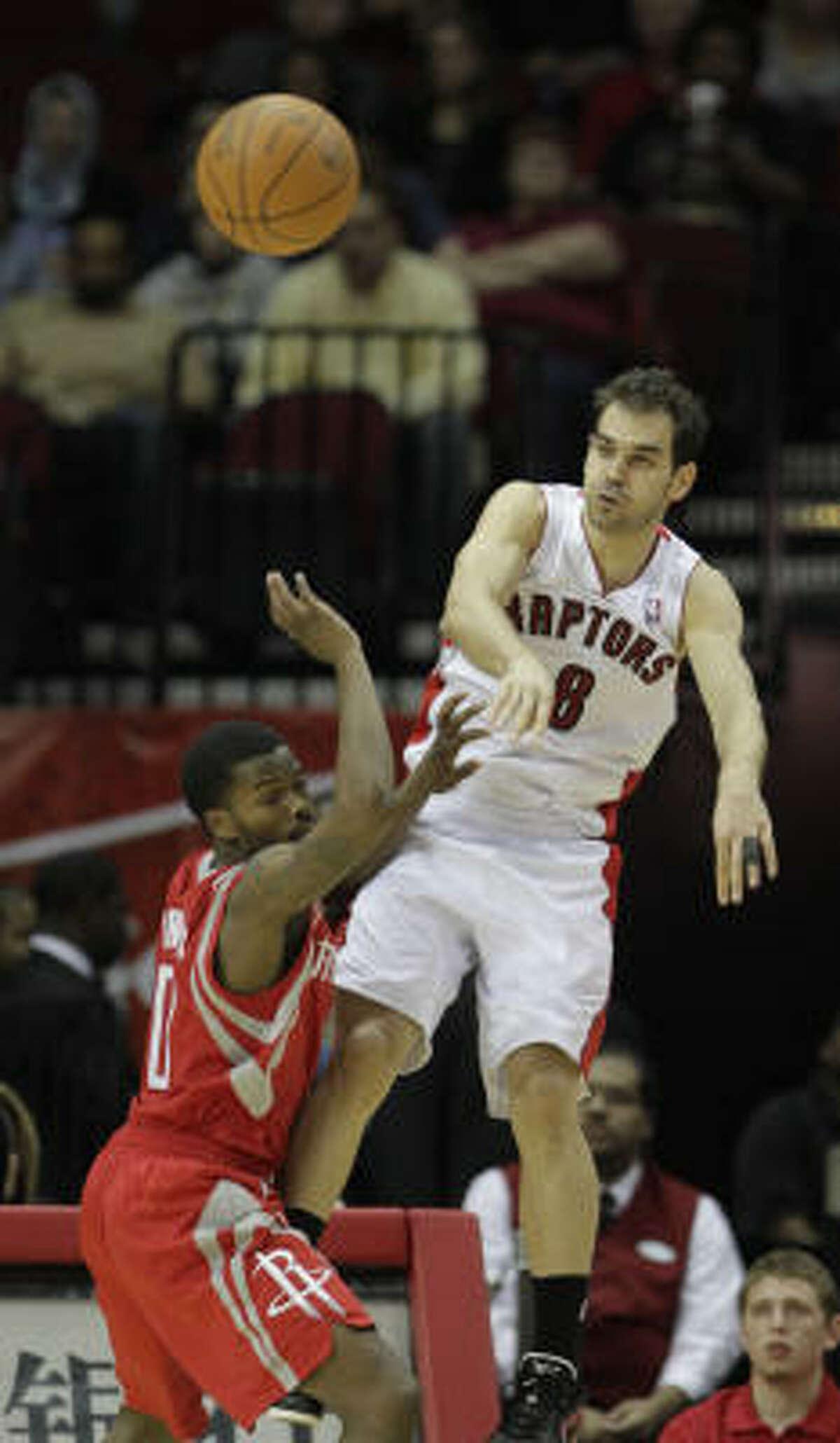 Toronto's Jose Calderon (8) passes the ball over Rockets guard Aaron Brooks.