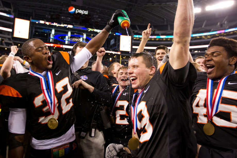 Running back Johnathan Gray (32) pours water on the head of teammate Rob Blowers (9) after Aledo defeated La Marque in the Class 4A Division II championship game at Cowboys Stadium. Gray rushed for 320 yards and eight touchdowns. Photo: Smiley N. Pool, Chronicle