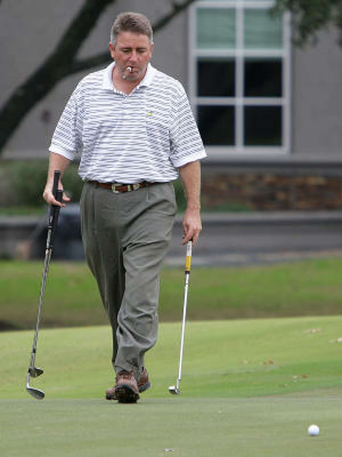 Craig Phillips smokes a cigar while eyeing the seventh hole.