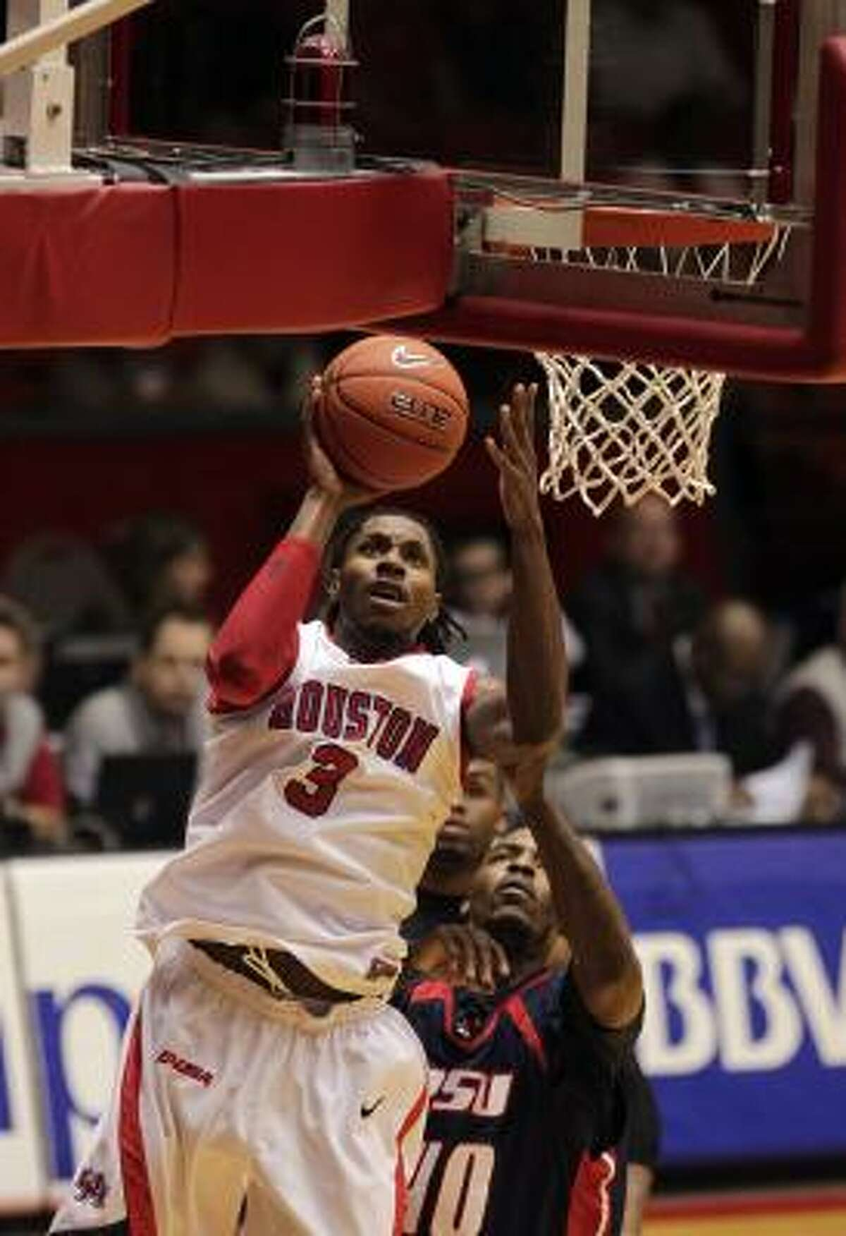UH forward Maurice McNeil (3) drives to the basket past Rogers State's Larry Cox in the first half. McNeil finished with a double-double of 25 points and 13 rebounds.