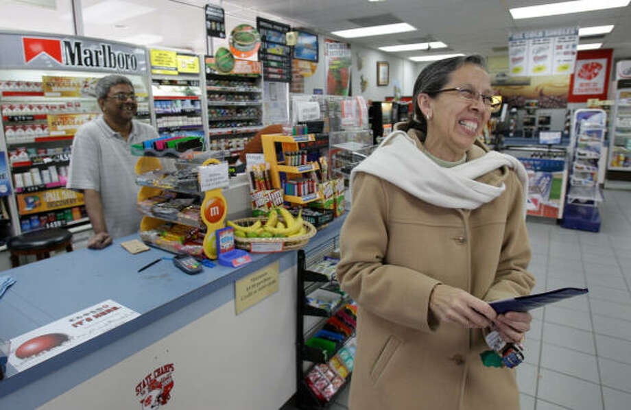 Terri Stout of Richmond shares a laugh with clerk Habib Wadsaria after buying a Lotto ticket Saturday from the Short Stop Market, 5304 E. Fifth, in Katy. The store sold a $144 million winning Mega Millions ticket for Friday night's drawing.  Photo: Melissa Phillip, Chronicle