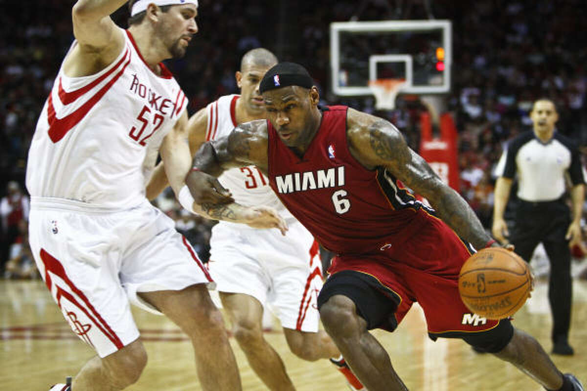 Heat forward LeBron James (6) drives past Rockets center Brad Miller (52) and forward Shane Battier during the first half of Wednesday's game at Toyota Center.
