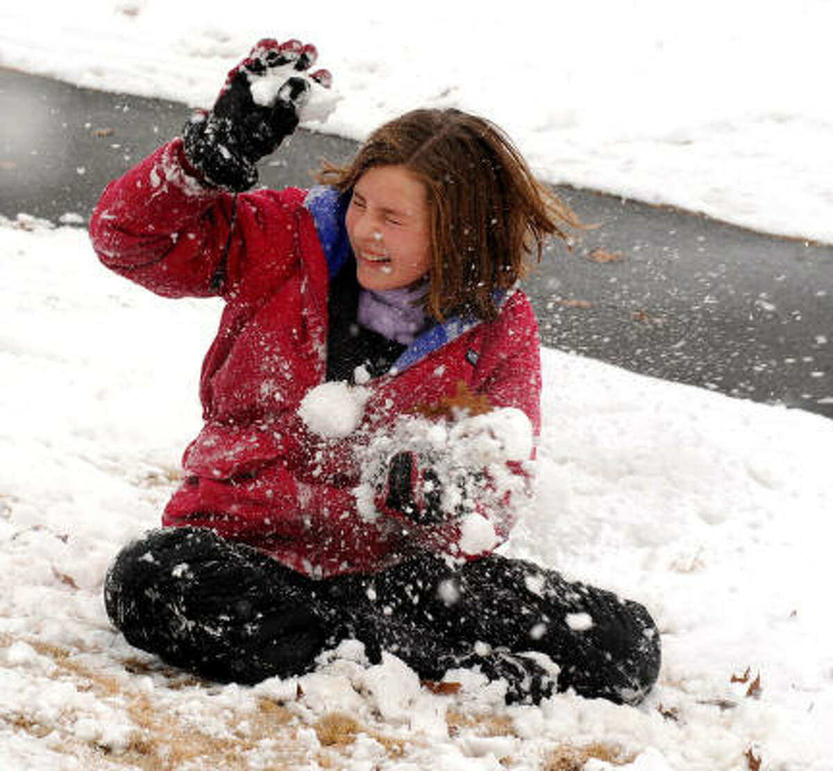 Alyssa Gibson winces as she takes a direct hit from a snowball thrown by her brother Nathan in a snowball fight at Warriors Path State Park in Kingsport, Tenn., Sunday.