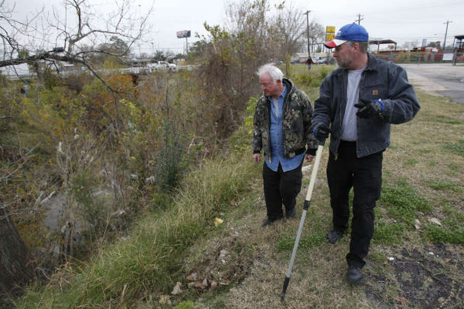 Members of Texas Equusearch Ron Overman of Montgomery, left,  and Joseph Hopkins of Pearland, right, look along White Oak Bayou in Houston near 610 and the intersection of Link and Enid for Jonathan Foster, 12, who has been missing since he was last seen on Dec. 24 near the area of N. Shepherd and 43rd. Photo: Melissa Phillip, Houston Chronicle