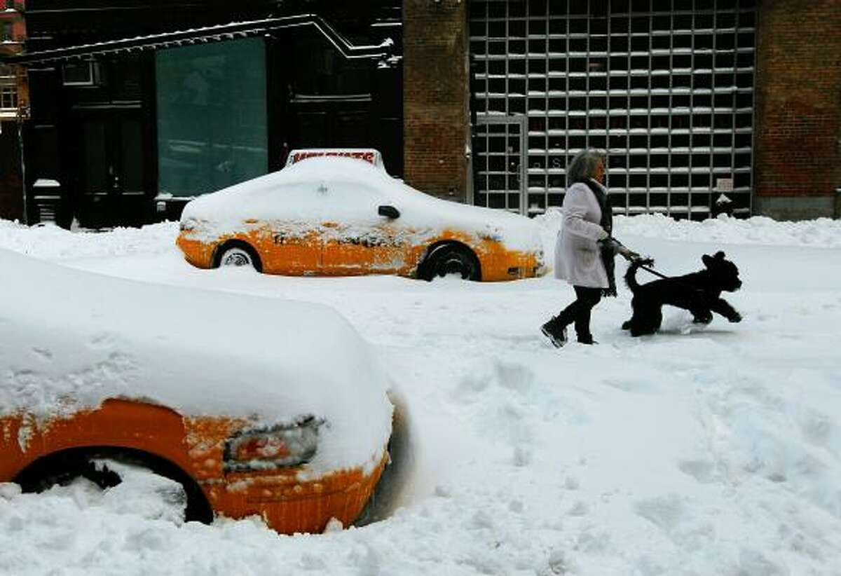 A woman walks her dog between snowed-in taxicabs following a major blizzard in Manhattan's Greenwich Village neighborhood Dec. 27 in New York CIty.