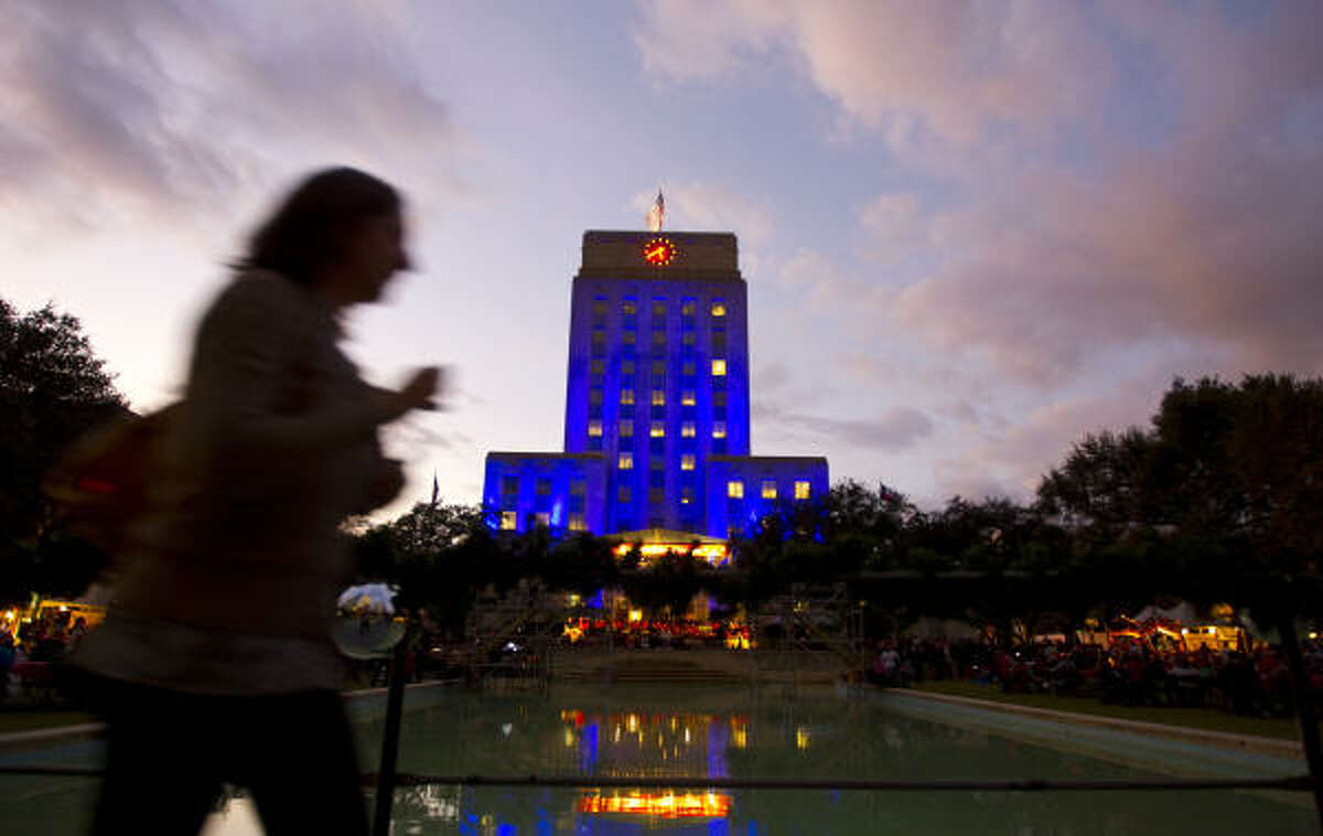People walk in front of City Hall which was lit in different colors during the Mayor's Holiday Celebration.