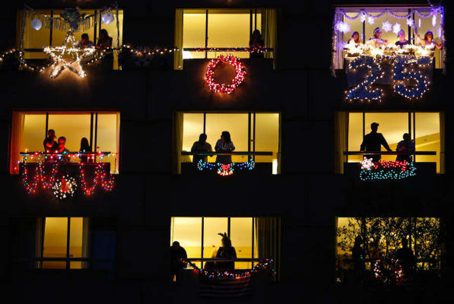 Hotel patrons look out their windows after decorating them for the Hilton Houston Post Oak Balcony Decorating Contest. Since the novel coronavirus began spreading throughout Houston, occupancy rates have plummeted, causing hotels like the Hilton Houston Post Oak to ask for relief on their loans. Photo: Michael Paulsen, Houston Chronicle