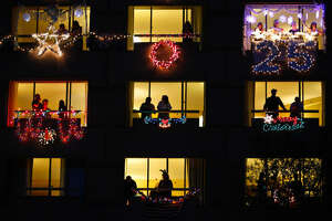 Hotel patrons look out their windows after decorating them for the Hilton Houston Post Oak Balcony Decorating Contest during the 25th annual Uptown Holiday Lighting.