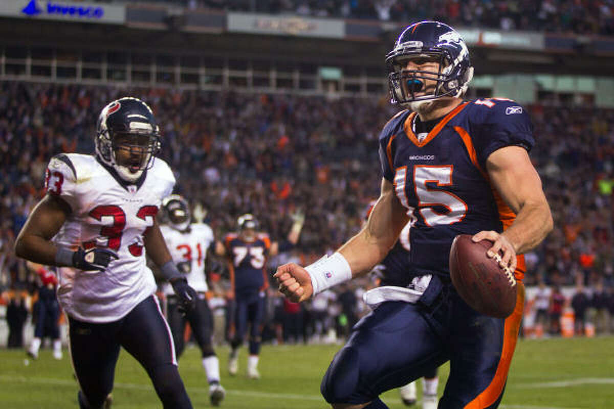 Denver Broncos quarterback Tim Tebow celebrates as as he runs past Houston Texans safety Troy Nolan (33) on a 6-yard touchdown run the fourth quarter.