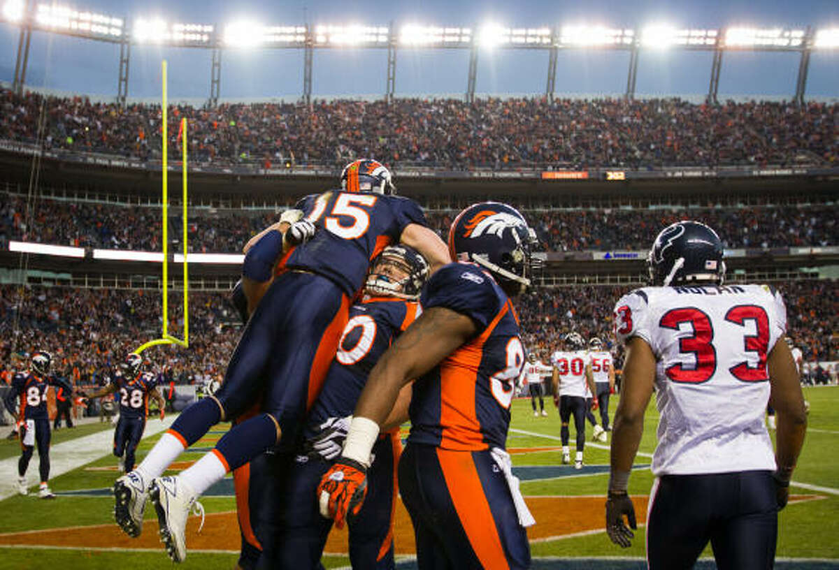 Denver Broncos quarterback Tim Tebow (15) celebrates with center J.D. Walton (50) after he scored past Houston Texans safety Troy Nolan (33) on a 6-yard touchdown run.