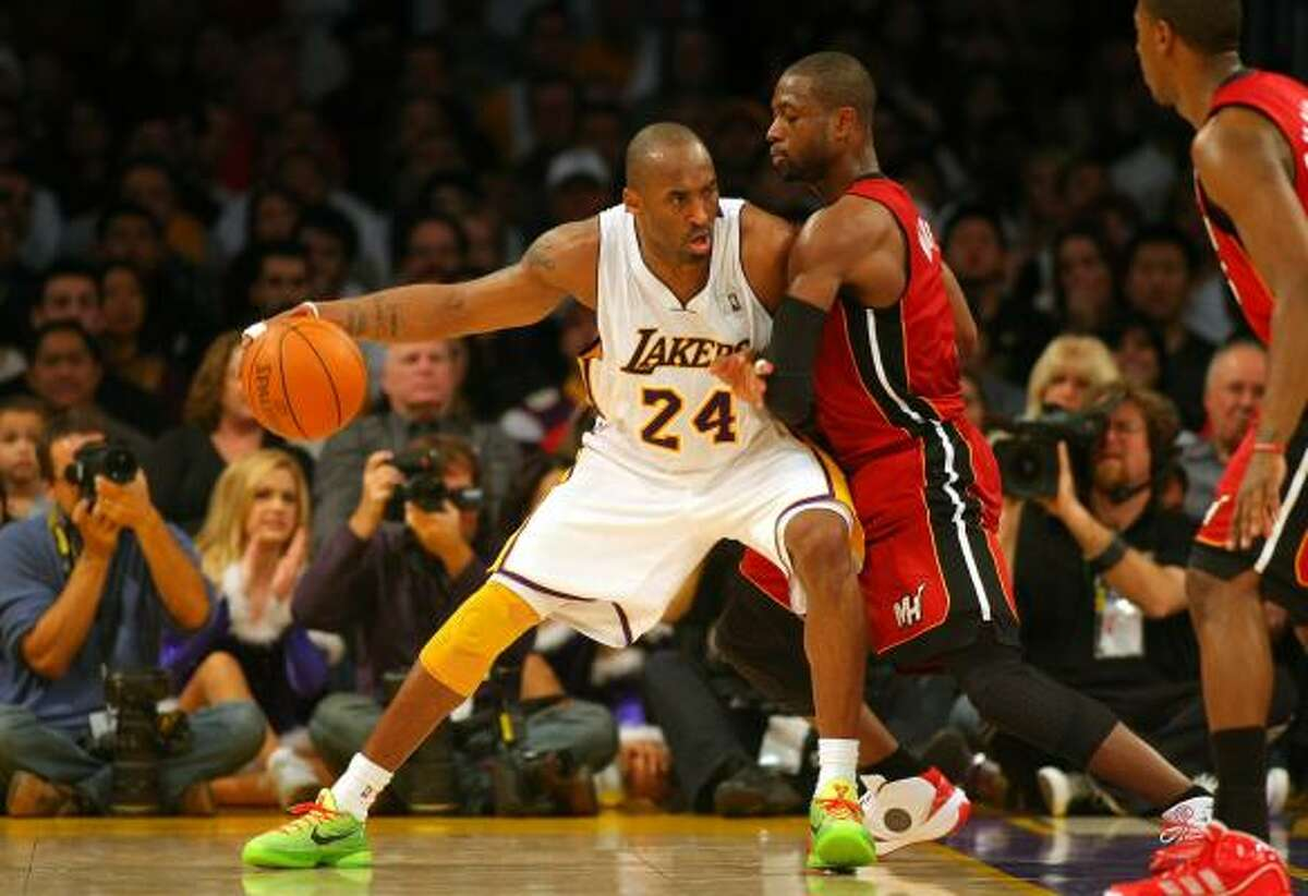 Lakers guard Kobe Bryant (24) backs down Heat guard Dwyane Wade during the first half.