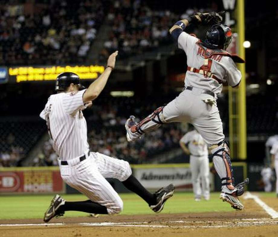 Aug. 30: Astros 3, Cardinals 0Astros right fielder Hunter Pence, left, slides safely into home plate to score as Cardinals catcher Yadier Molina leaps to catch the ball. Photo: David J. Phillip, AP