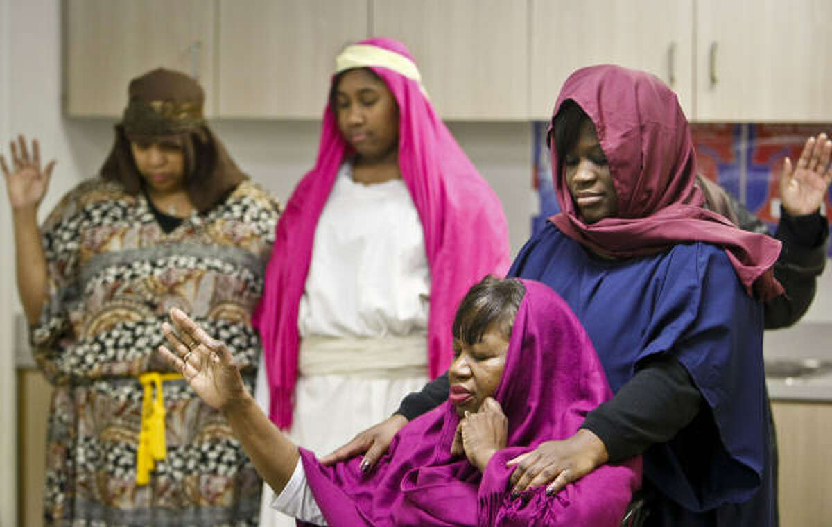 (From left) Performers Stephanie Ford, her daughter Skylar, Rosalyn Johnson and Pam Johnson pray before taking the stage at Church Without Walls.