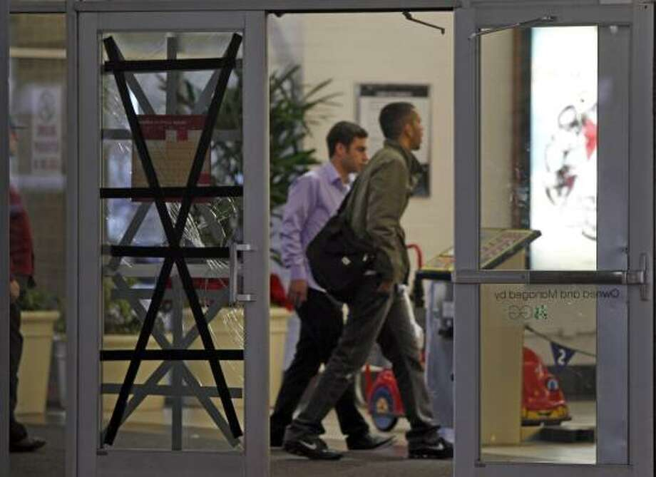People enter Deerbrook Mall as workers repair one of the doors broken after shoppers who had lined up before dawn became unruly while they waited outside to buy new Nike Air Jordan shoes Thursday, Dec. 23, 2010, in Humble. Photo: Melissa Phillip, Chronicle