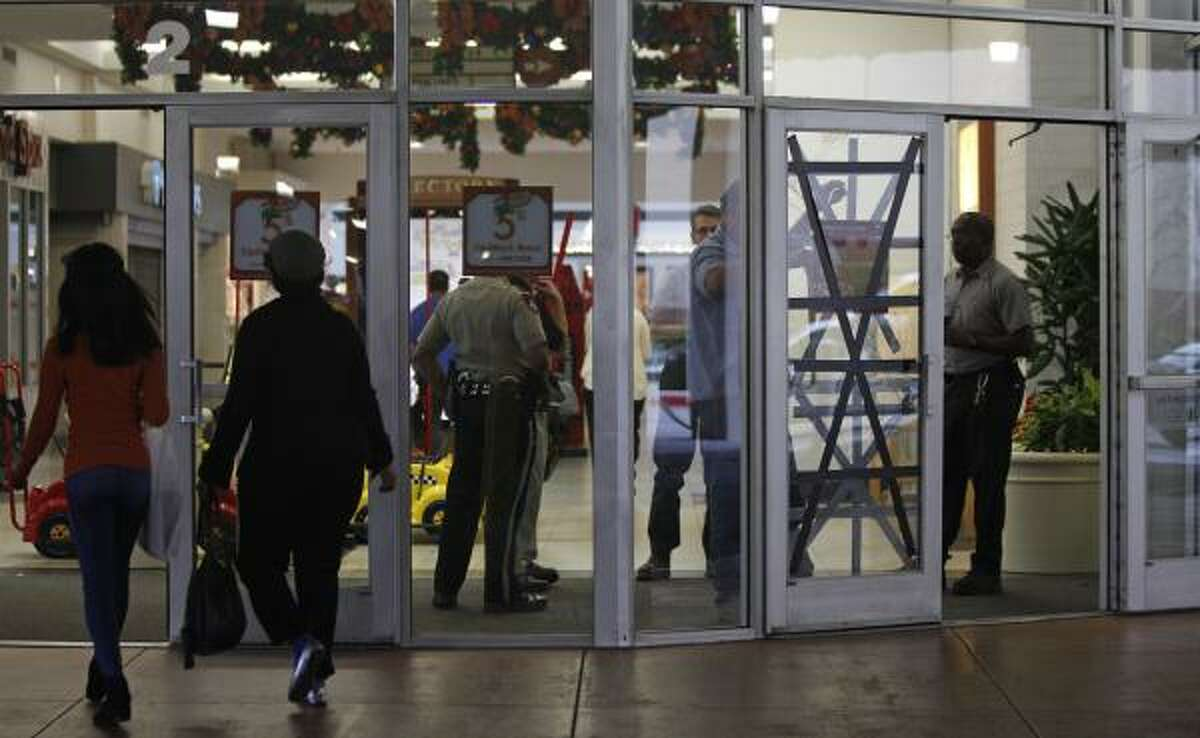People enter Deerbrook Mall as workers repair one of the doors broken after shoppers who had lined up before dawn became unruly while they waited outside to buy new Nike Air Jordan shoes Thursday, Dec. 23, 2010, in Humble.