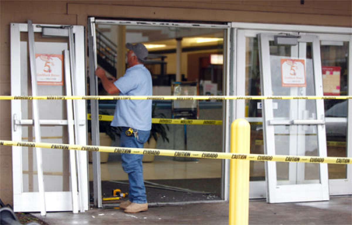 Danny Sims with Binswanger Glass repairs a door at Deerbrook Mall after shoppers who had lined up before dawn apparently became unruly while they waited outside to buy new Nike Air Jordan shoe Thursday, Dec. 23, 2010, in Humble.