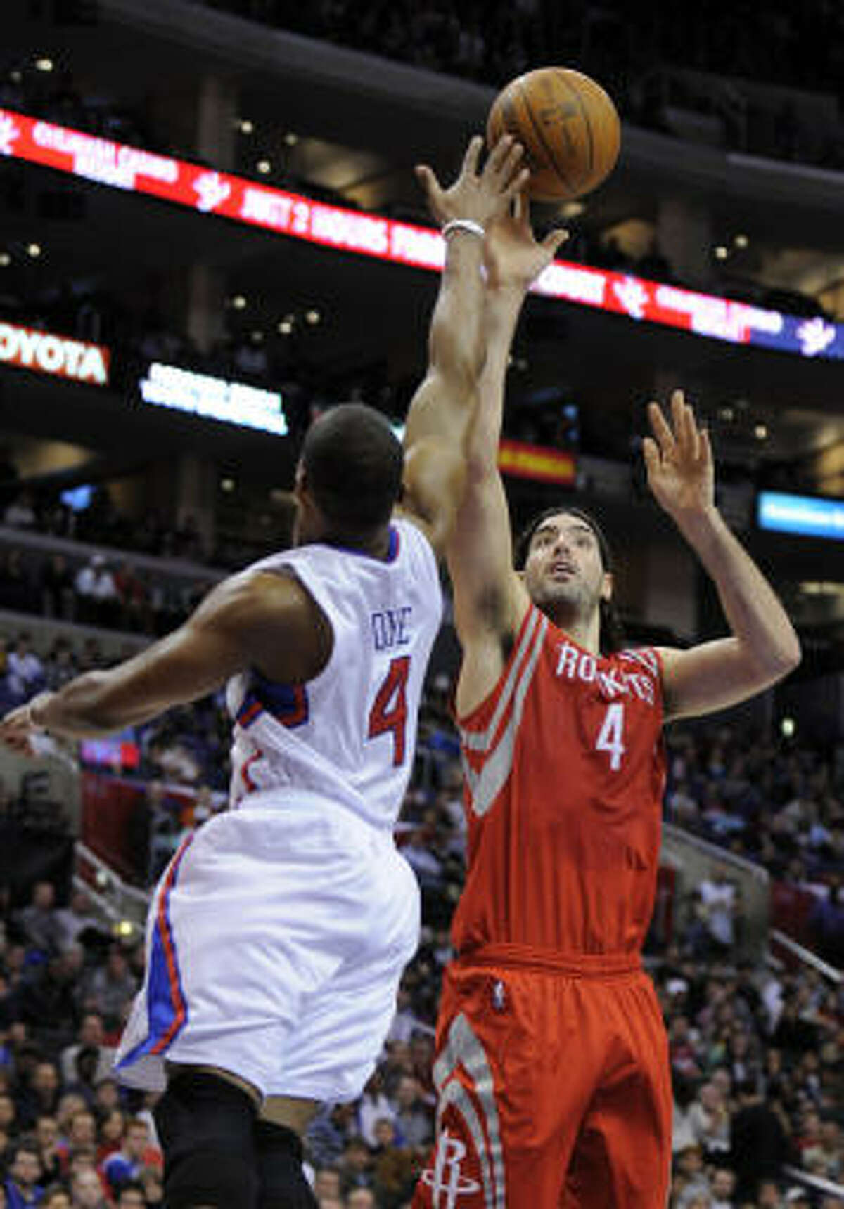 Rockets forward Luis Scola, right, shoots over Clippers guard Randy Foye during the first half.
