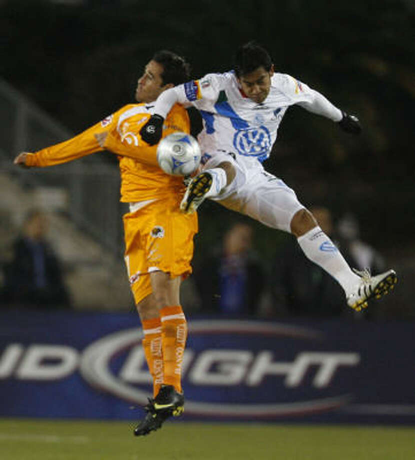 Puebla forward Carlos Ruiz, right, goes up for the ball against Jaguares defender Oscar Razo in the first half. Photo: Julio Cortez, Chronicle