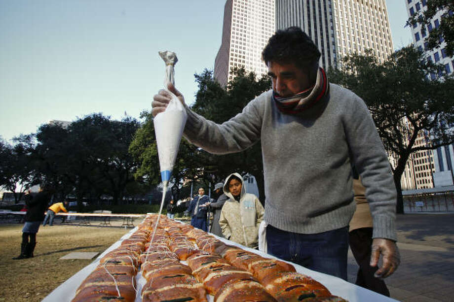 Elias Duran, the lead baker Saturday, applies frosting on the giant pastry at Hermann Park. Kings cake is a tradition, part of the Mexican holiday honoring the three wise men. Photo: Michael Paulsen, Chronicle