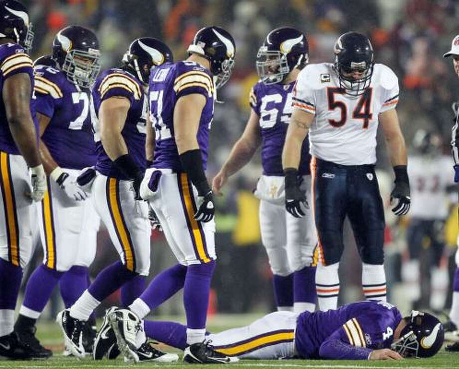 Dec. 20: Bears 40, Vikings 14 Chicago Bears linebacker Brian Urlacher looks down as Minnesota Vikings quarterback Brett Favre lies on the ground after being hit during the first half on Monday night. Photo: Andy King, AP