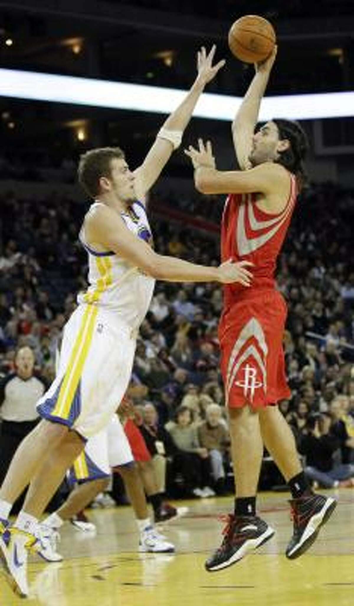 Rockets forward Luis Scola, right, shoots over Warriors center David Lee.