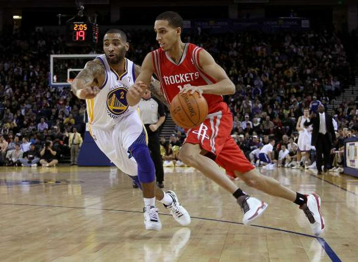Rockets guard Kevin Martin dribbles past Acie Law (2) of the Warriors.