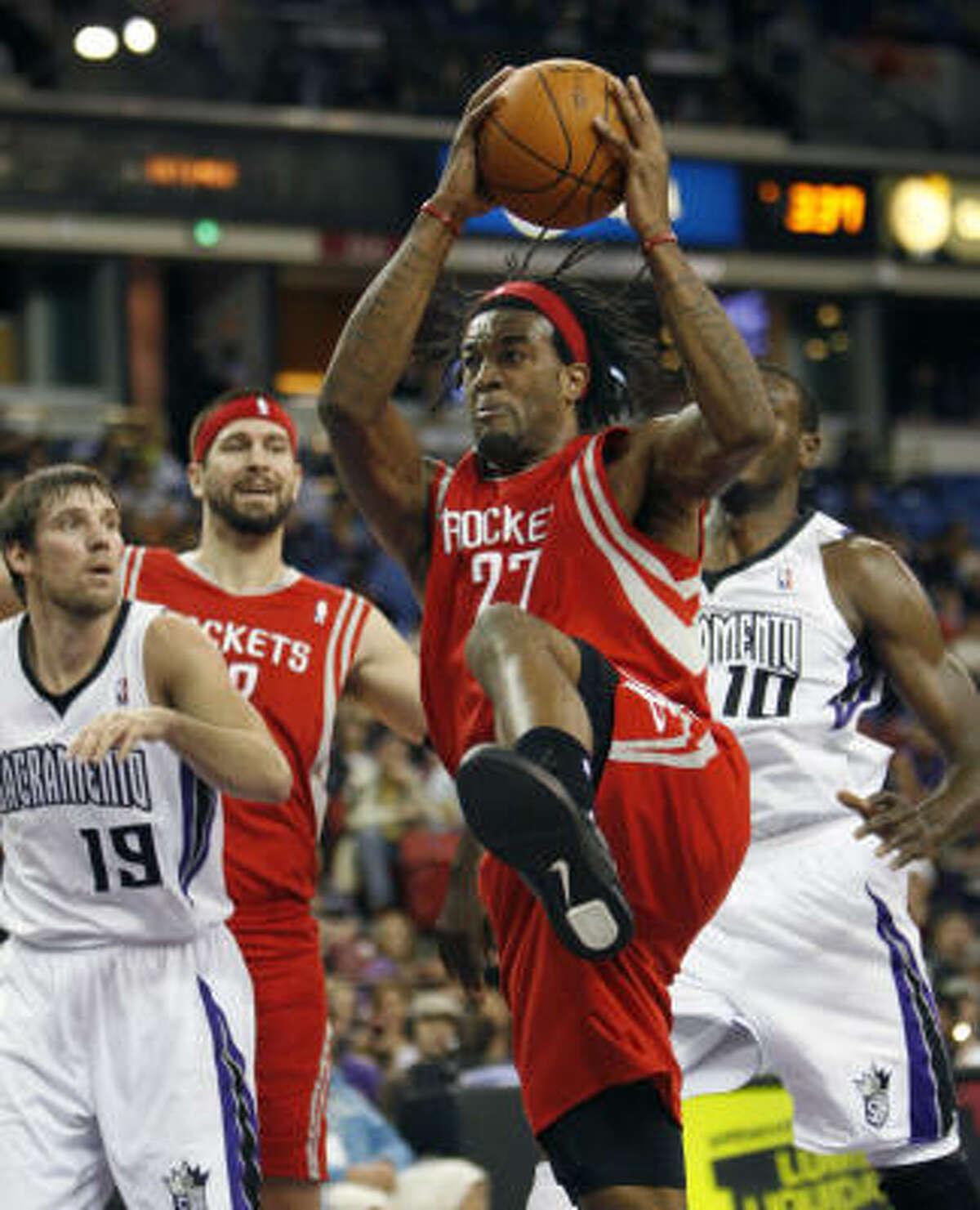 Rockets forward Jordan Hill pulls down a rebound against Kings guard Beno Udrih (19), and Samuel Dalembert during the first half.