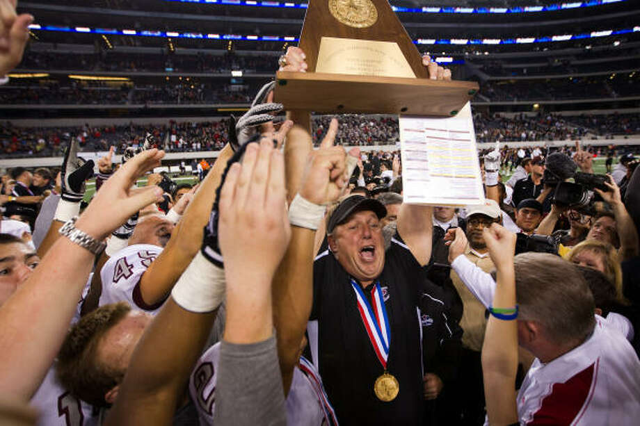Dec. 18 Class 5A Division I final: Pearland 28, Euless Trinity 24 Pearland head coach Tony Heath hoists the Class 5A Division I state championship trophy after the Oilers' upset win over Euless Trinity on Saturday night at Cowboys Stadium in Arlington. Photo: Smiley N. Pool, Chronicle