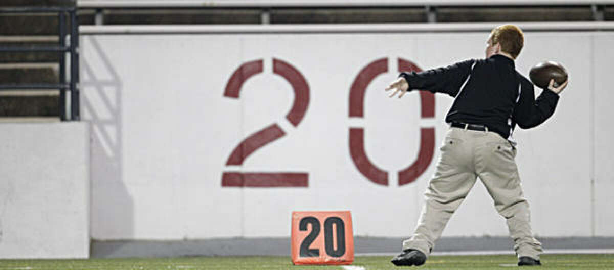 A ball boy for North Shore tosses a football before the start of the Class 5A, Division I Region III second round high school football playoffs between North Shore and Hightower High Schools.