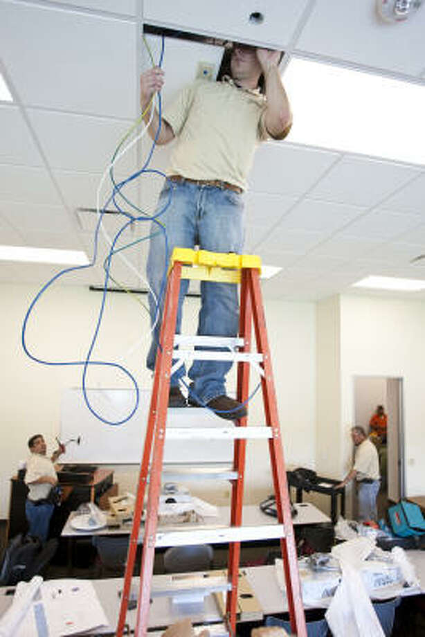 Ryan Carlet installs audio-visual equipment at the University of Houston-Clear Lake Pearland. Photo: Nick De La Torre, Chronicle