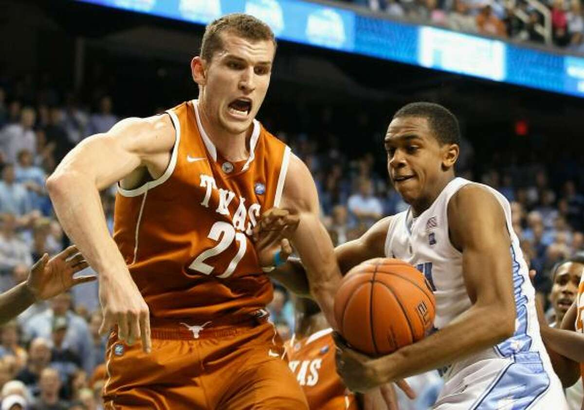 North Carolina's John Henson, right, grabs a rebound as Texas' Matt Hill goes for the ball.