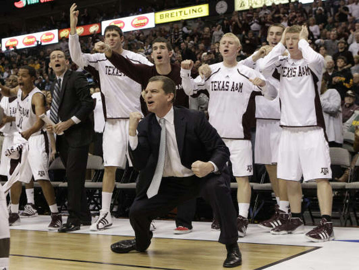 Texas A&M coach Mark Turgeon and the Aggies bench react at a shot in the second half.
