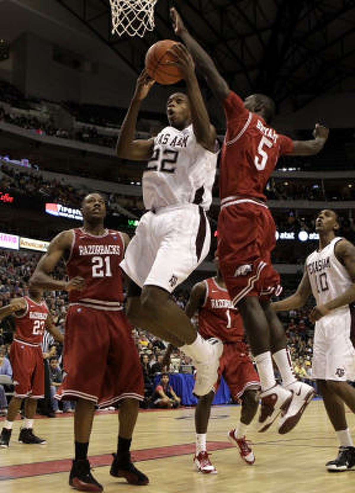 Texas A&M forward Khris Middleton drives to the basket past Arkansas forwards Delvon Johnson (21) and Glenn Bryant (5).