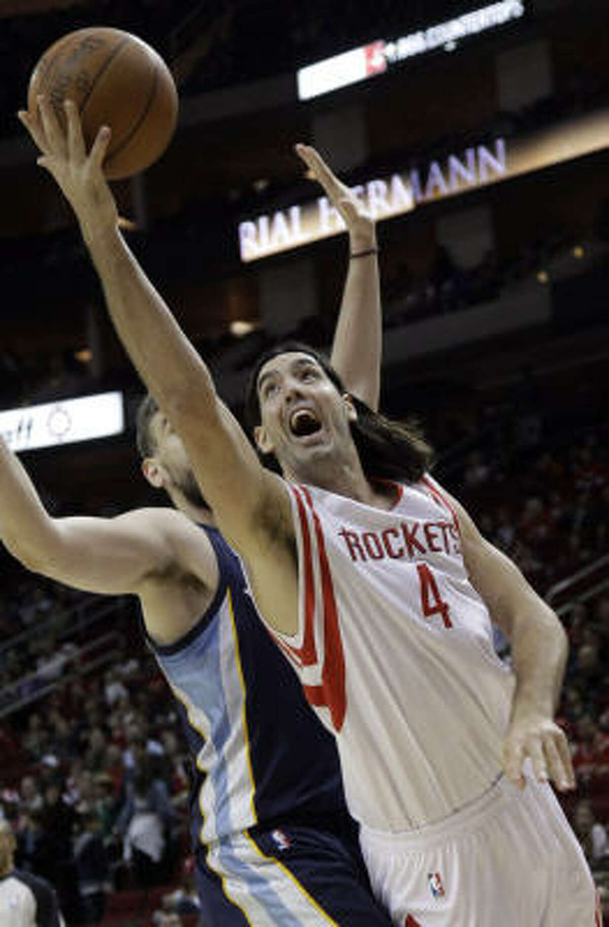 Rockets forward Luis Scola puts up a shot as Grizzlies center Marc Gasol, rear, defends during the first quarter.