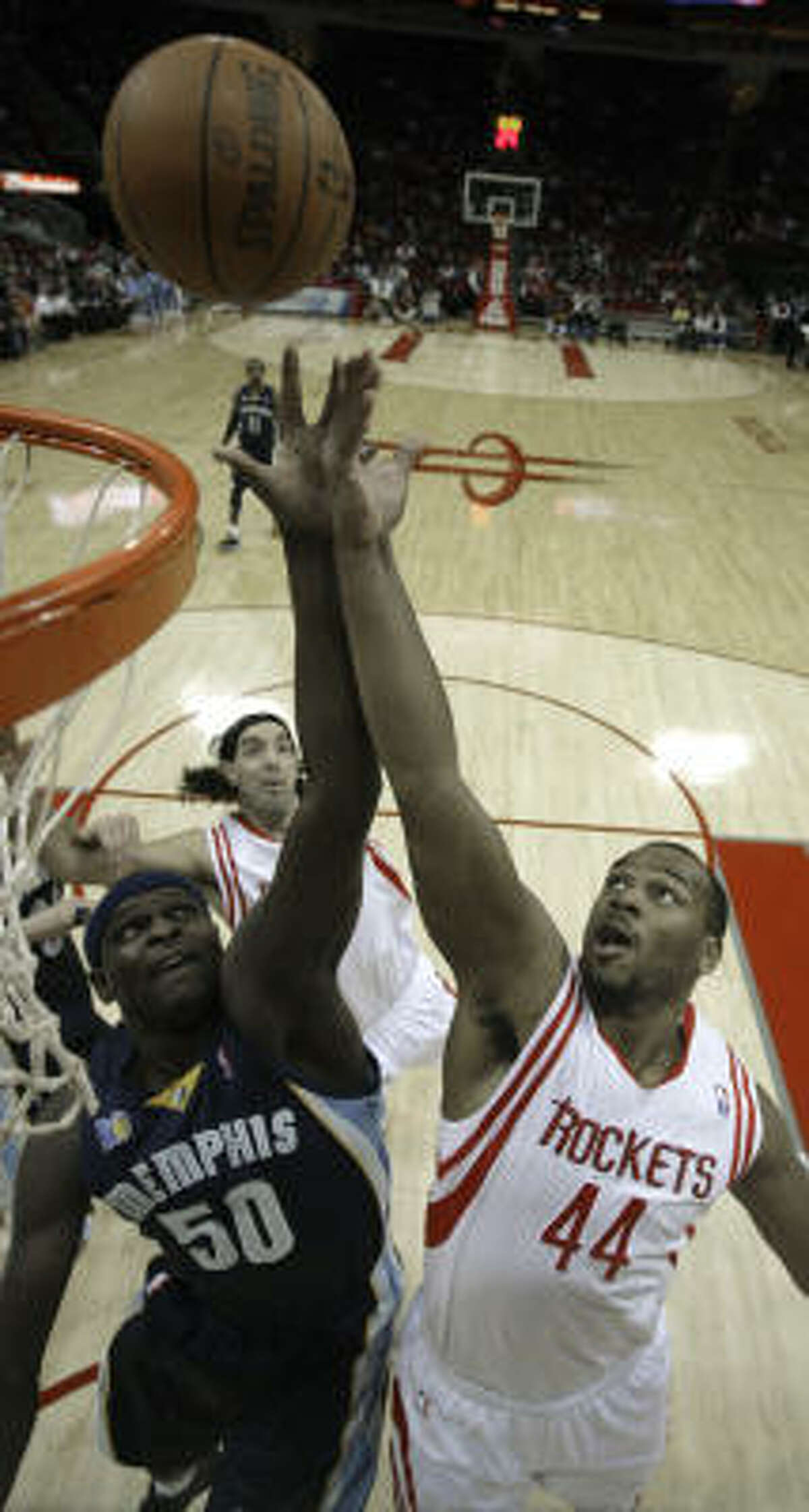 Grizzlies forward Zach Randolph, left, goes up for a rebound with Rockets forward Chuck Hayes during the first quarter.