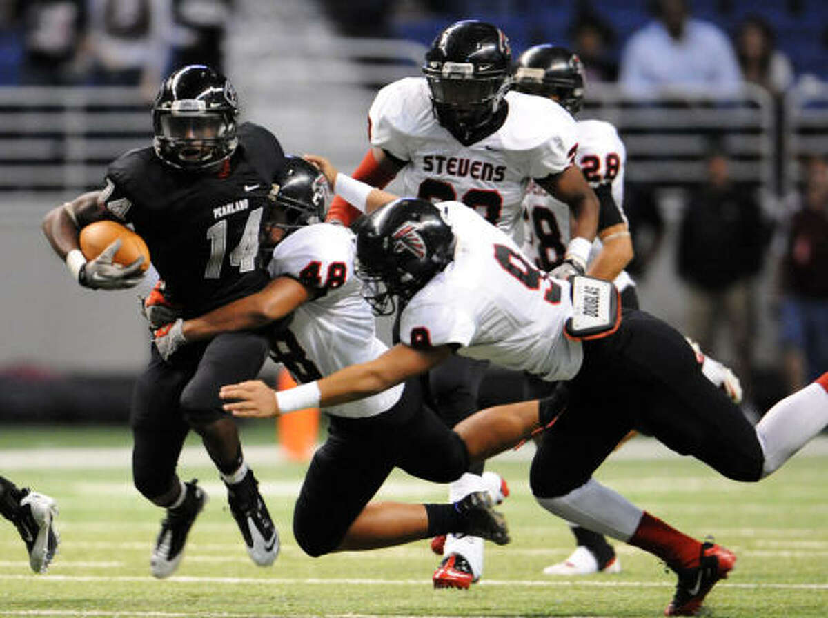 Pearland's Kevin Washington (14) is tackled by Stevens' Hector Monreal (48) and Tamoyia Morris (9).
