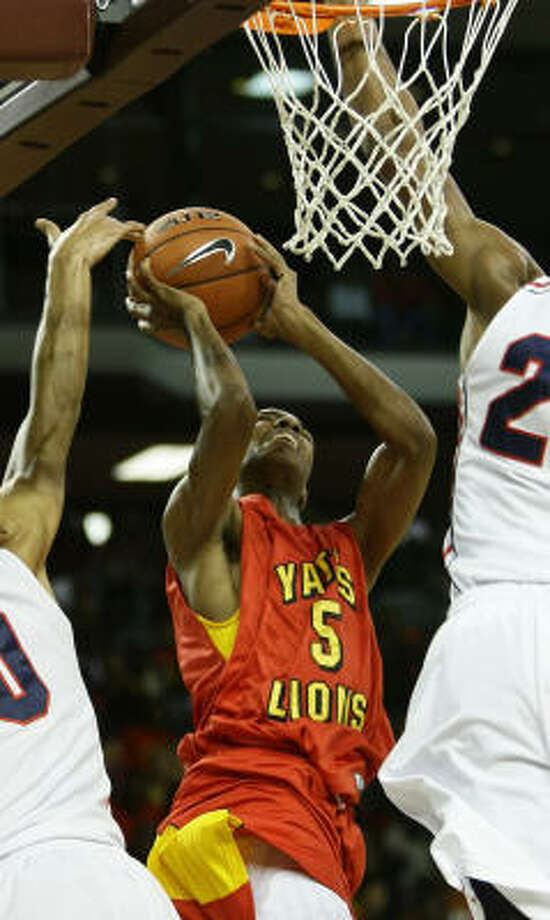 Yates' Shai Fields takes the ball to the basket over a pair of Findlay Prep defenders. Photo: Nick De La Torre, Chronicle