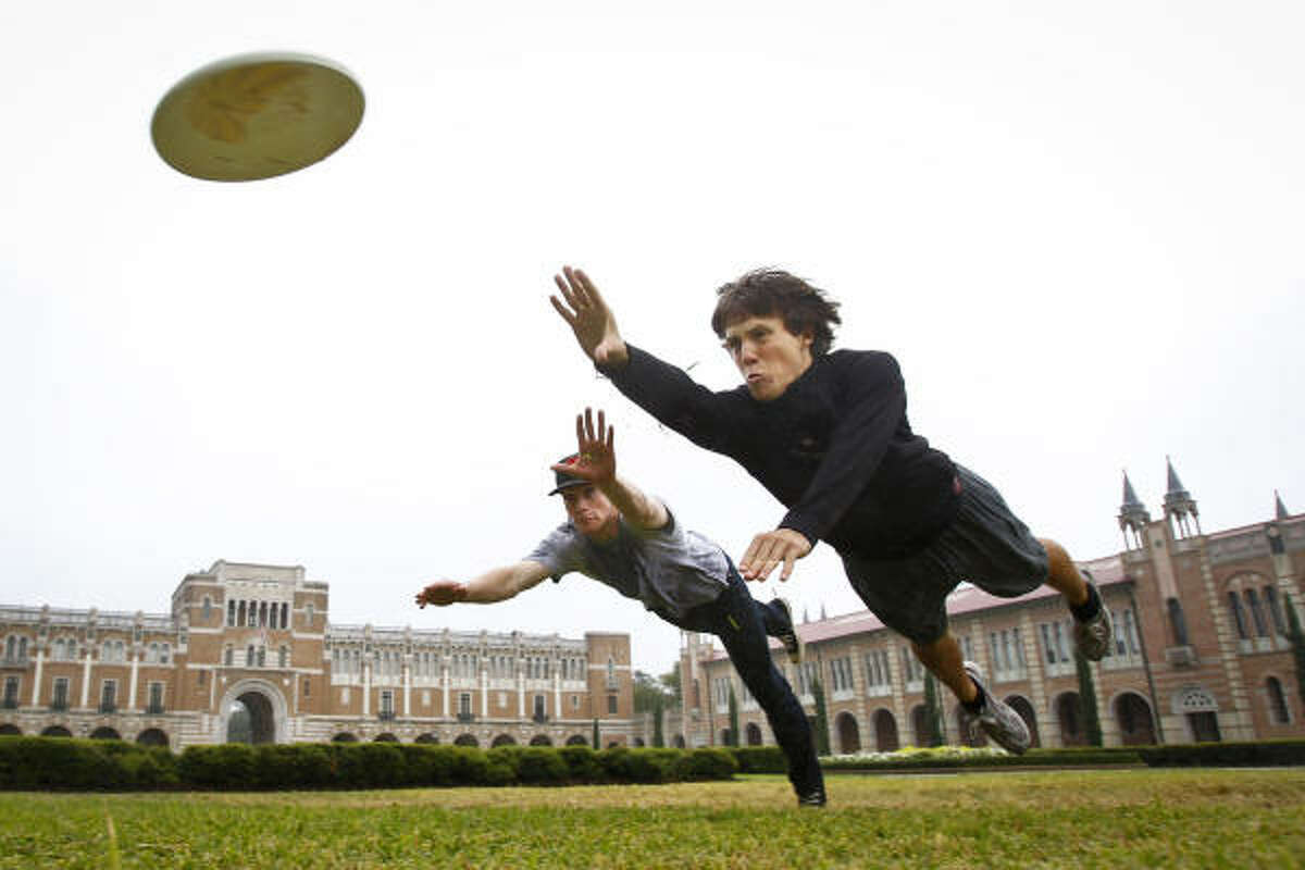 Harrison Schwarzer and Travis Martin stretch into the air for an ultimate frisbee as they practice a layout drill on a soggy patch of grass at Rice University Wednesday, Nov. 3, 2010, in Houston.