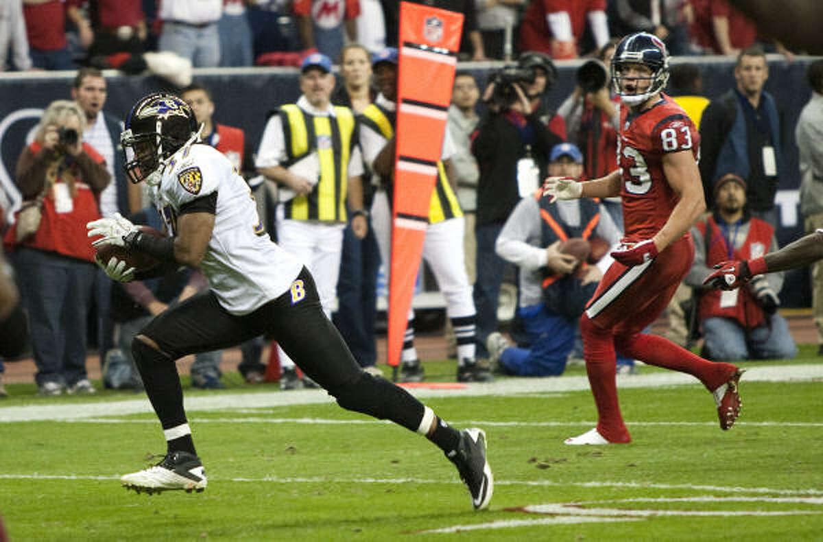Ravens cornerback Josh Wilson, left, runs past Texans wide receiver Kevin Walter as he returns an interception of a Matt Schaub pass 12 yards for a game-winning touchdown during overtime.