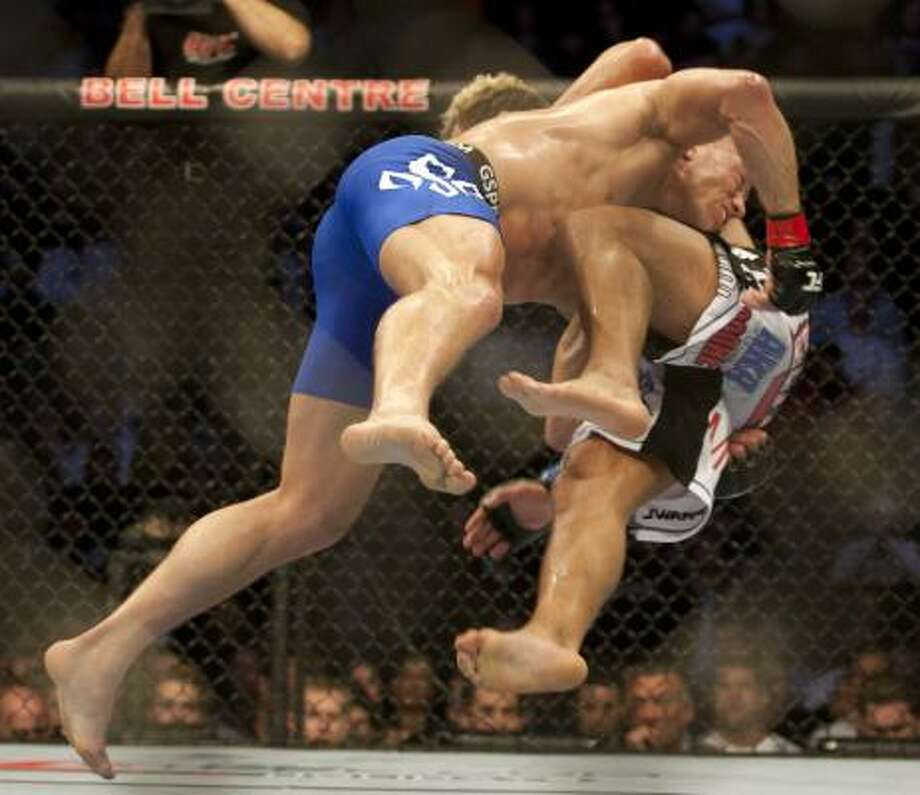 George St-Pierre, left, hurls Josh Koscheck to the mat. Photo: Ryan Remiorz, AP