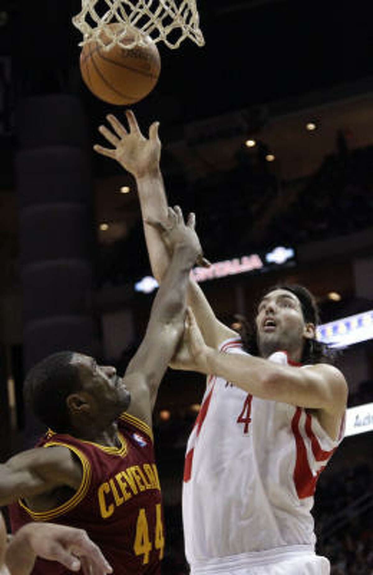 Rockets forward Luis Scola, right, shoots as Cleveland Cavaliers forward Leon Powe defends during the third quarter.
