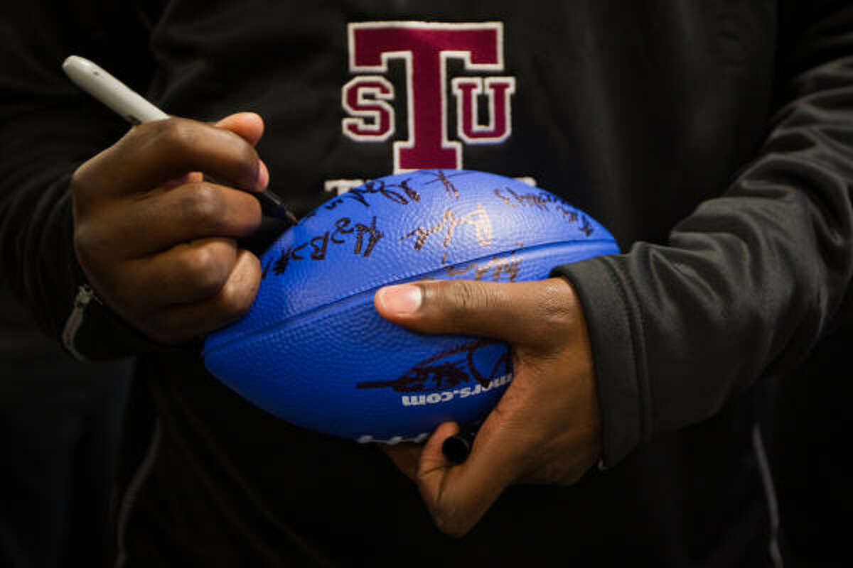 A Texas Southern Tigers player autographs a ball for patients.